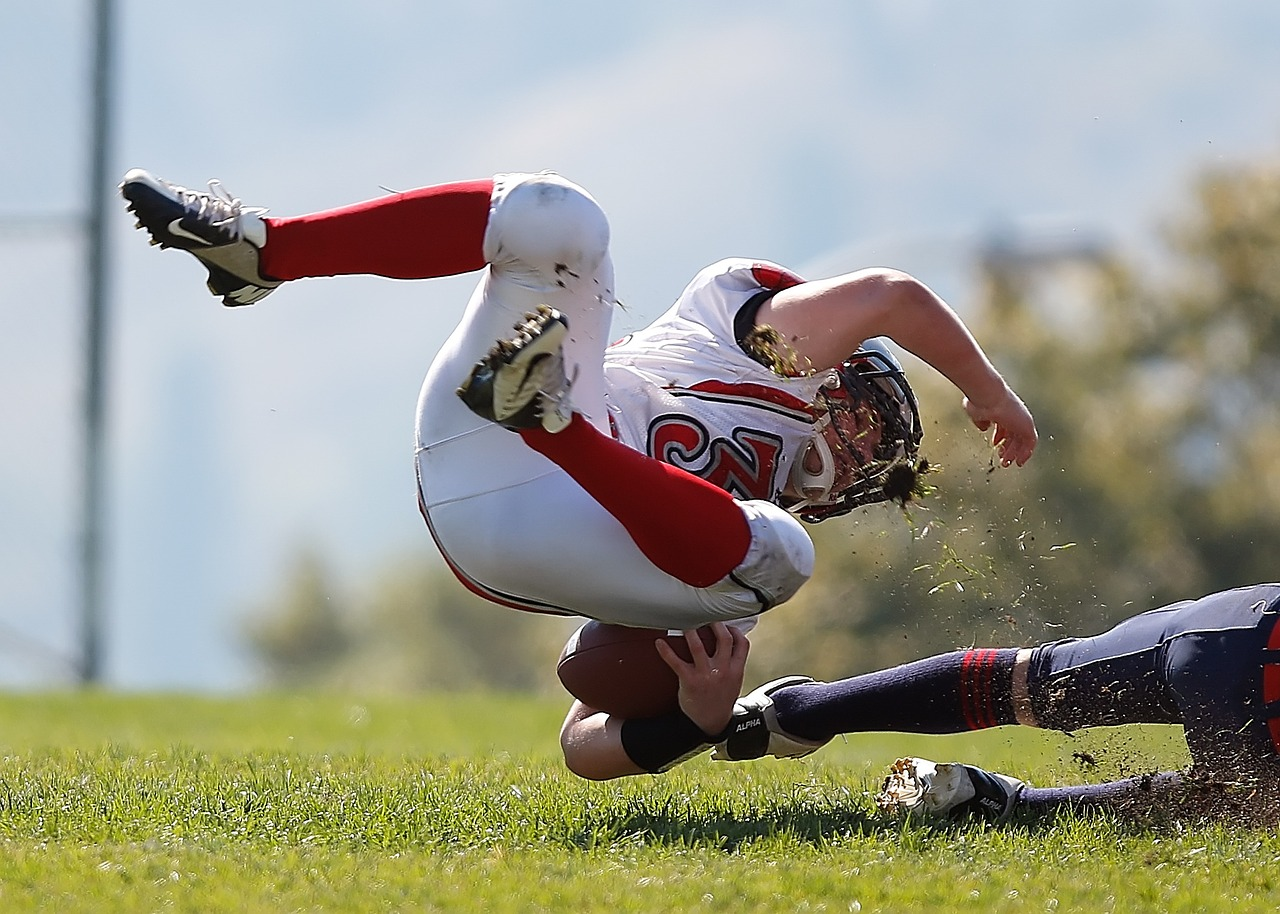Football playing being tackled